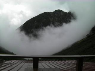 雨の涸沢ヒュッテのテラスから、ガス(雲)から突如現れた山