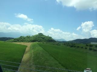 【巨石】田園風景の中に点々と黒々とした巨石や小さな丘がある。