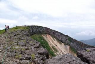 【反対側の端からの景色】山頂がなだらかなのがわかる、このあたりの崖ギワに大きくヒビがあるのも見える。