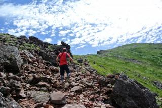 【頂上付近】前方の緑の「崖」は爆裂火口の「縁(へり)」、道は縁ぞいにまっすぐに頂上へと向かう。