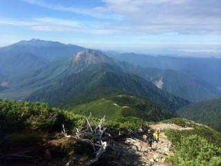 【焼岳から西穂高山荘】西穂高山荘の少し上から撮った写真、茶色の頭が焼岳で、「あいだの縦走路」は木に覆われている。