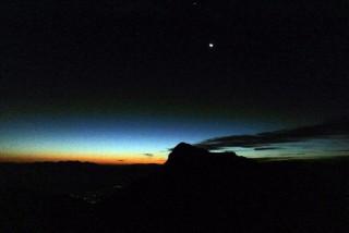 """【夜明け前】月とその上に見える小さな輝点は""""木星""""、地平線は夜明けの光があがってきた。"""
