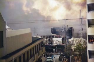 【長田区では倒壊とともに火災も発生した】煙の向こうに傾いた建物も見える。